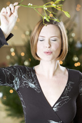 A woman waiting for kiss under the mistletoe