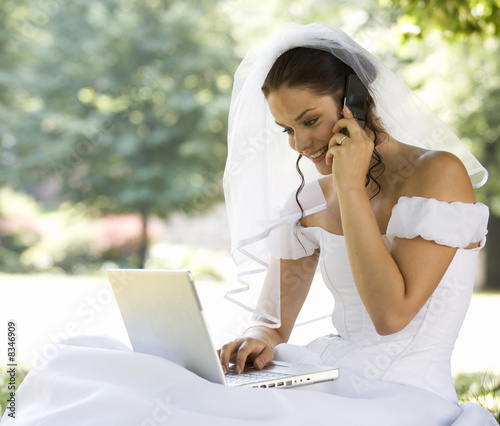 A bride using a laptop and mobile phone