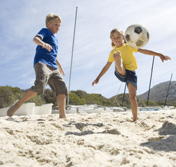 Two children playing football on a beach