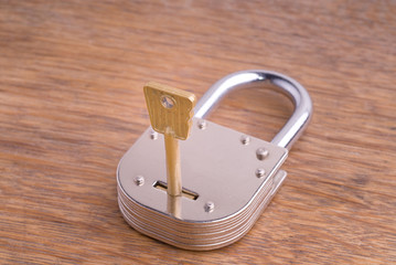 Closed Old Style Padlock with Key on a Wooden Table
