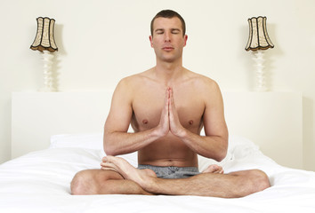 Young man on bed practicing yoga