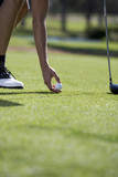 Man playing golf, close-up of feet on the tee
