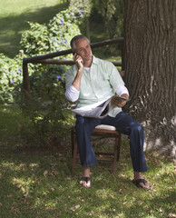 Man talking on a mobile phone, sitting next to a tree