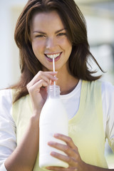 A woman drinking milk through a straw