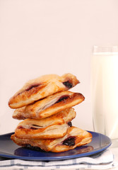 Stack of blueberry turnovers with milk