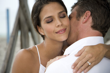 A bride and groom kissing on a beach