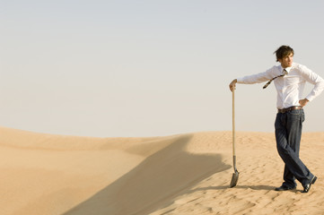 A young man standing in the desert with a spade
