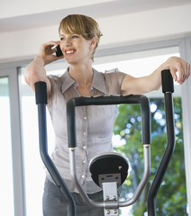 A businesswoman in a gym using a mobile phone