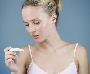 A young woman looking at a pregnancy test