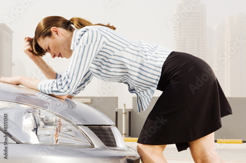 A businesswoman leaning on the bonnet of a car