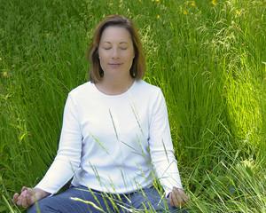 Woman Meditating in Field of Grass