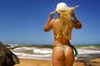 Bikini girl walking to the ocean wearing string beach wear