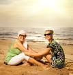 Two beautiful women sitting on the beach