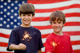 Boys at Twilight Holding Sparklers in Front of Flag