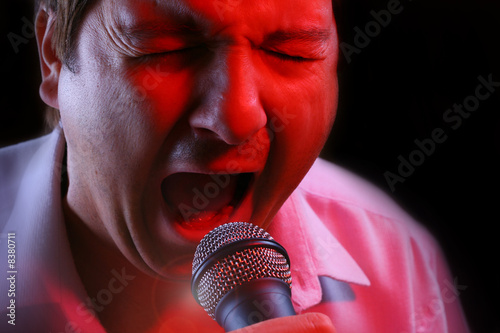Karaoke singer on a scene - using a microphone.