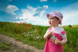 Leinwanddruck Bild Baby-girl on a lane amongst a field