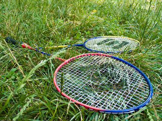 Two badminton rackets in grass