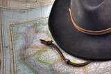 felt hat over vintage, warn out map of South America poster