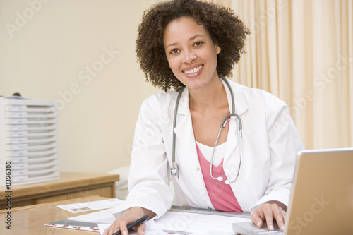 Doctor with laptop in doctor's office smiling