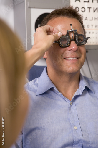 Optometrist in exam room with man in chair smiling