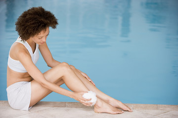 Woman sitting poolside using shower puff on leg