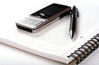 Pen, spiral notepad and mobile phone on white background