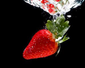 Rote Erdbeere fällt ins Wasser