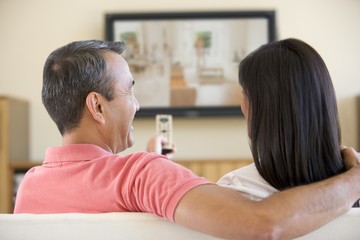 Couple in living room watching television laughing