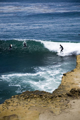 Central California surfer and withered cliff.