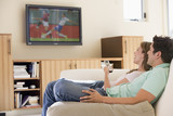 Fototapety Couple in living room watching television
