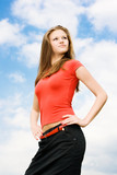 Young proud woman on sky background poster