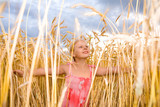 Little girl in a wheat field. Against the backdrop of blue sky. poster