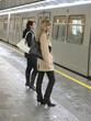 Zwei junge Mädchen, Frauen warten auf die einfahrende U-Bahn.