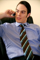Young businessman sitting  and talking on cell phone