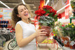 young woman holds pot with rose in shop