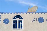 Satellite TV dish on muslim house poster