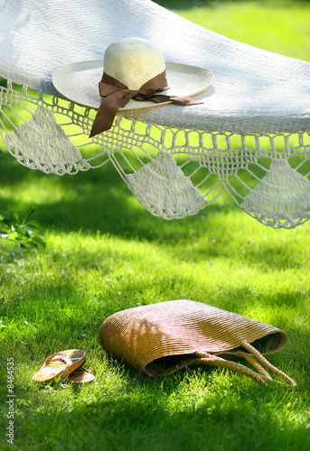 Straw hat with brown ribbon laying hammock
