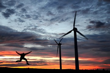 wind farm at dusk with a jumping man - a silhouette