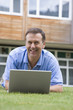 Man using laptop while lying in grass on campus