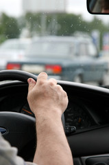 man holds a steering wheel of the car