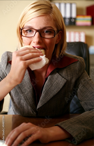 Young woman eating at her desk