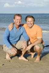 A happy gay couple on the beach.