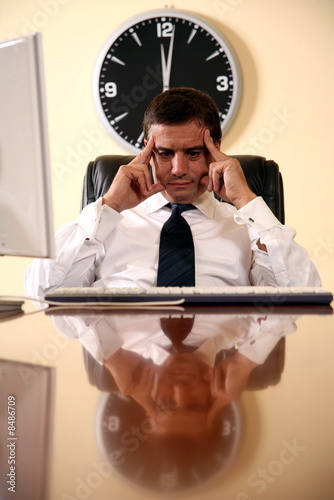 Businessman sitting at his desk lost in thought