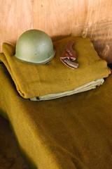 Military bed with helmet and pistol