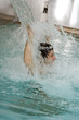Young man standing under water spray in spa pool