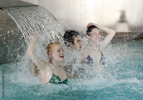 Young people standing under water spray in spa pool