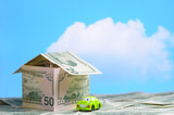 House built of money and a toy car poster