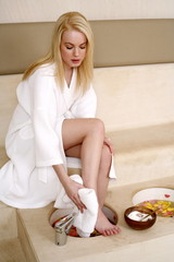 A young woman enjoying a foot bath with rose petals