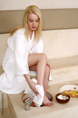 A young woman enjoying a foot bath with rose petals