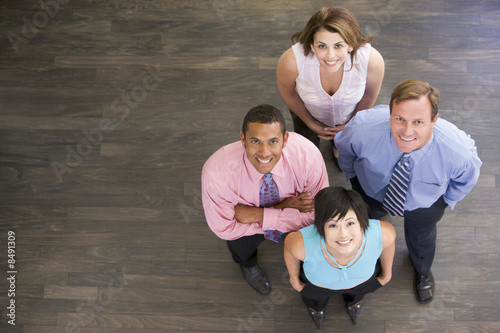 Four businesspeople standing and smiling
